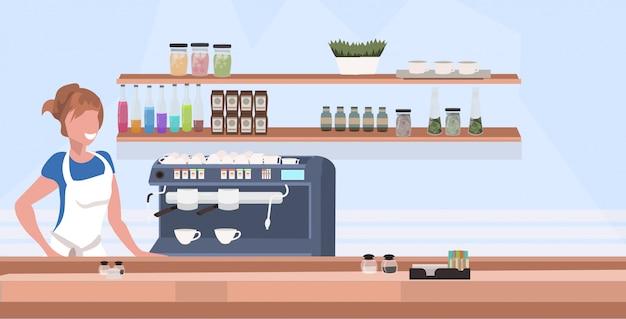 De serveerster barista van de vrouwenkoffie in schort die zich bij het tegen horizontale horizontale vlakke portret van de bureau moderne koffiewinkel bevinden
