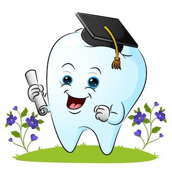 De tand draagt de afgestudeerde hoed en houdt een illustratiepapier vast
