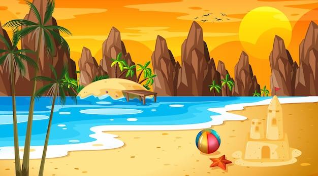 De tropische scène van het strandlandschap met zandkasteel in zonsondergangtijd