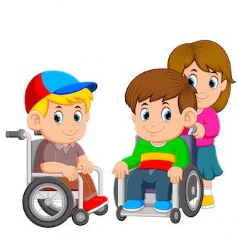 De twee jongens gebruiken de rolstoel met het meisje erop