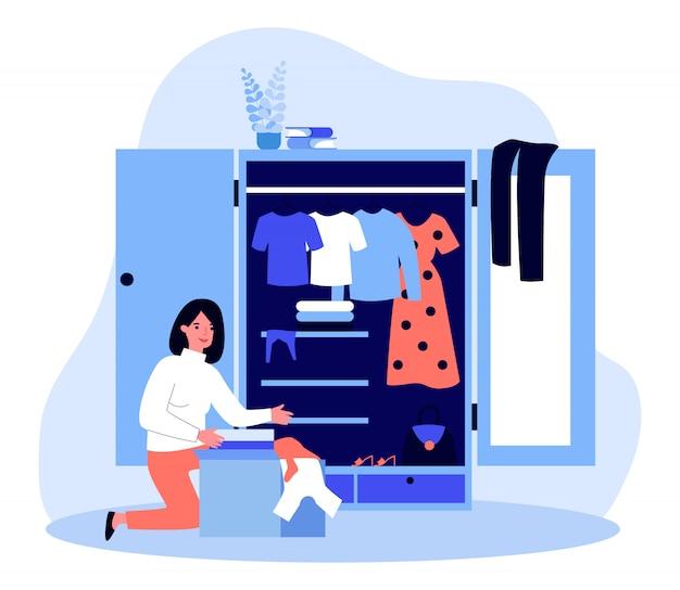 De verpakkingsdoos van de vrouw met kleren bij haar garderobe