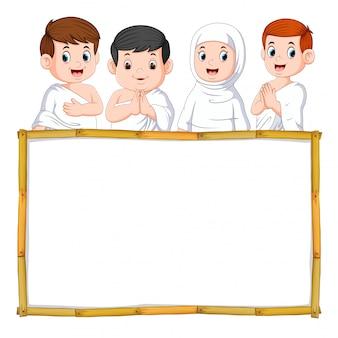 De vier kinderen gebruiken de witte doek boven het houten frame