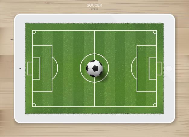 De voetbalbal van het voetbal op voetbalgebied van tabletvertoning.