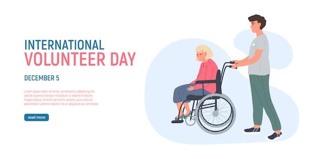 De vrijwillige jonge man loopt een oudere grijze haired vrouw op een rolstoel. 5 december de internationale vrijwilligersdag. maatschappelijk werkers die voor senioren zorgen. zorg voor ouderen