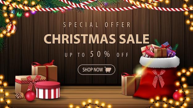 De vrolijke banner van de kerstmisverkoop met santa claus-zak met stelt en houten muur met kerstmisdecor voor