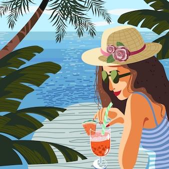 De vrouw op een achtergrond van blauwe overzees drinkt fruitcocktail onder tropische bomen
