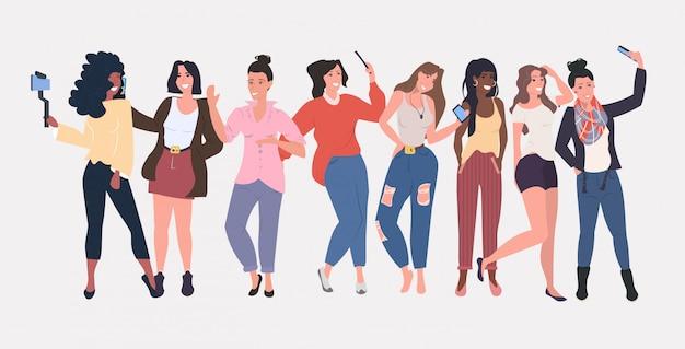 De vrouwengroep die de meisjes van het mengelingsras zich verenigen die smartphonecamera gebruiken die selfie foto nemen sociale media netwerk blogging concept volledige lengte horizontaal