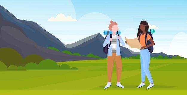 De vrouwenwandelaars koppelen aan van de de reiskaart van de rugzakholding de meisjes die van het de mengelingsras route de reizigers van het wandelingsconcept plannen op het landschaps van achtergrond stijgingbergen volledige lengte horizontale vlakte
