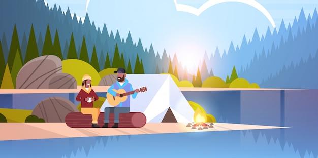 De wandelaars die van paartoeristen bij de kammens het spelen gitaar voor meisjeszitting ontspannen op logboek wandelingsconcept zonsopgang landschap natuur rivier bos bergen horizontale achtergrond