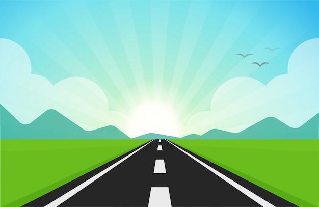 De weg die door groene velden snijdt