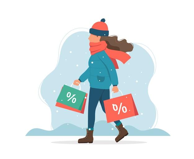 De winterverkoop, meisje met het winkelen zakken in de winter.