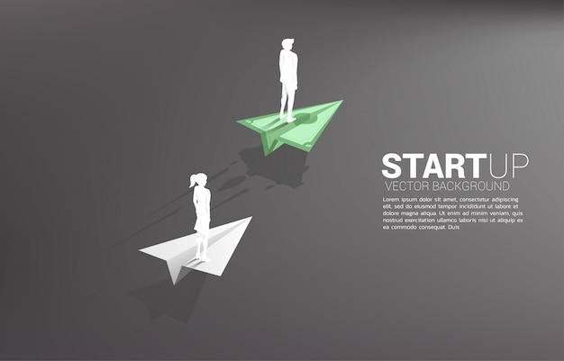 De zakenman en de onderneemster die zich op het origamidocument vliegtuig van het geldbankbiljet bevinden zijn beweging sneller dan het wit. businessconcept van snelle rijstrook voor het verplaatsen en opstarten.