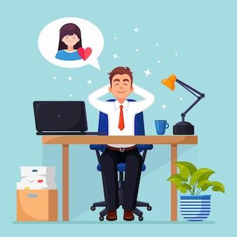 De zakenman ontspant en droomt over vrouw met rood hart bij bureaustoel.