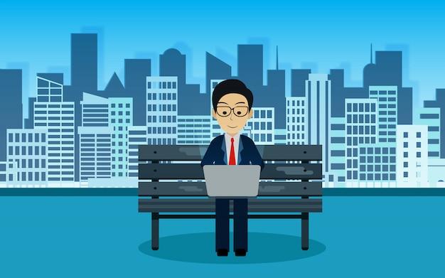 De zakenmanzitting op de stoel die een computernotitieboekje in het park erachter spelen is de stad