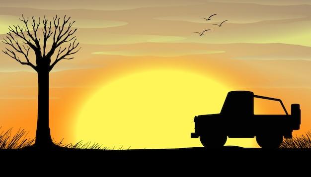 De zonsondergangscène van het silhouet met een vrachtwagen
