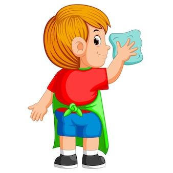 Deligent jongen die een dagelijkse activiteit doet om met de blauwe handdoek schoon te maken