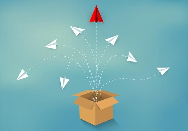 Denk buiten de doos. papieren vliegtuigje rood en wit uitgeworpen uit doos bruin