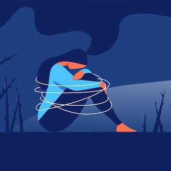 Depressieve vrouw zit met arm gewikkeld rond knieën