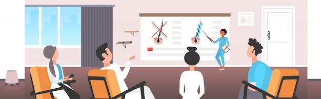 Dermatoloog die de structuur van de haarzakjes uitlegt voor de behandeling van haarkeratine-versterkende behandelingen door het team van artsen