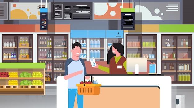 Detailhandelaar kassier bij kassa supermarkt