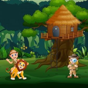 Dierenverzorger kinderen spelen met leeuw onder de boomhut