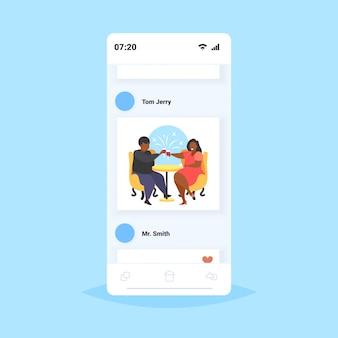 Dik overgewicht paar zittend aan café tafel zwaarlijvige man vrouw het drinken van wijn ongezonde levensstijl zwaarlijvigheid concept mensen plezier smartphone scherm online mobiele app