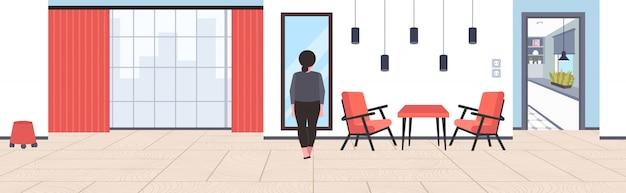 Dik overgewicht zakenvrouw kijken naar reflectie in spiegel triest zwaarlijvig meisje ongezonde levensstijl zwaarlijvigheid concept modern kantoor interieur horizontaal achteraanzicht volledige lengte