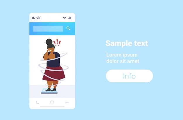 Dikke vrouw met overgewicht staande weegschalen ongezonde levensstijl zwaarlijvigheid gewichtscontrole concept zwaarlijvig verdrietig meisje met uitroeptekens smartphone scherm online mobiele app volledige lengte horizontaal