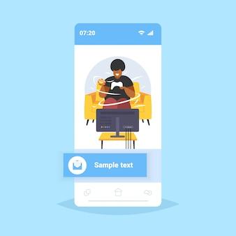 Dikke zwaarlijvige man eet hamburger met joystick gamepad overgewicht man speelt videogames op tv zwaarlijvigheid ongezonde voeding concept smartphone scherm online mobiele app