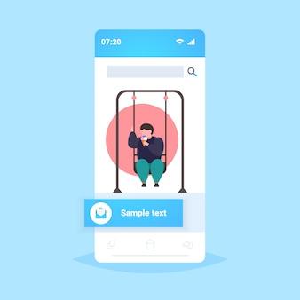 Dikke zwaarlijvige man swingend en ijs eten ongezonde voeding obesitas concept overgewicht man zittend op schommel plezier smartphone scherm online mobiele app