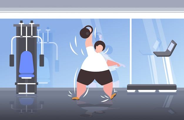 Dikke zwaarlijvige man tillen kettlebell overgewicht man doen oefeningen training training gewichtsverlies concept moderne sportschool interieur