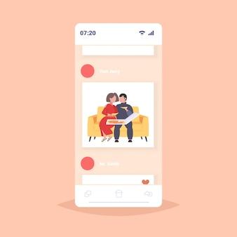 Dikke zwaarlijvige man vrouw zittend op de bank pizza eten fastfood ongezonde voeding concept paar plezier ontspannen op de bank smatphone app online mobiele app volledige lengte