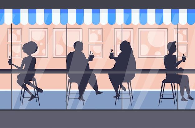 Dikke zwaarlijvige mensen silhouetten koffie drinken bespreken tijdens vergadering mannen vrouwen zitten aan balie zwaarlijvigheid concept moderne straat café buitenkant