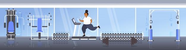 Dikke zwaarlijvige vrouw draait op loopband overgewicht afro-amerikaanse meisje cardiotraining training gewichtsverlies concept moderne sportschool studio interieur