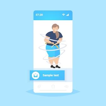 Dikke zwaarlijvige vrouw haar taille meten verdrietig overgewicht meisje met meetlint gewichtsverlies zwaarlijvigheid concept smatphone scherm online mobiele app volledige lengte