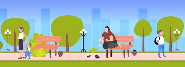 Dikke zwaarlijvige vrouw met brood en het voeden van kudde duiven overgewicht meisje, zittend op een houten bankje zwaarlijvigheid concept openbaar park stadsgezicht