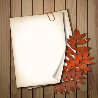 Document blad met de herfstbladeren op houten textuur als achtergrond.