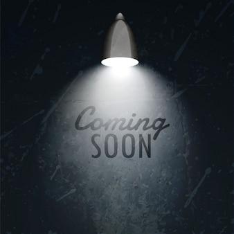 Donkere muur met gloeiende lamp en binnenkort tekst