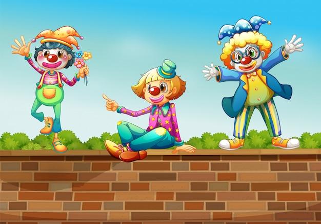 Drie clowns boven de muur