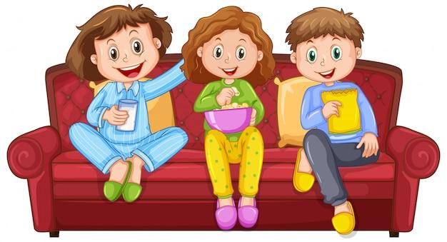 Drie gelukkige kinderen eten snacks op de bank