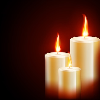Drie kaarsen op donkere achtergrond.