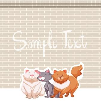 Drie katten en bakstenen muur