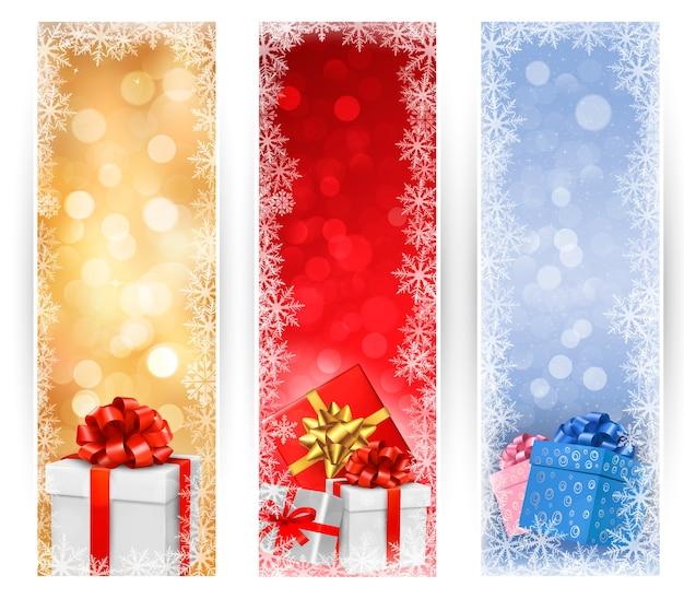 Drie kerstbanners met geschenkdozen en sneeuwvlokken.