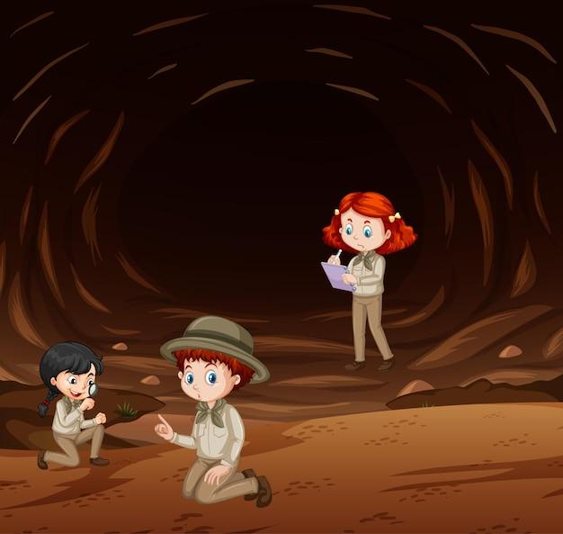 Drie kinderen verkennen de natuur in de grot