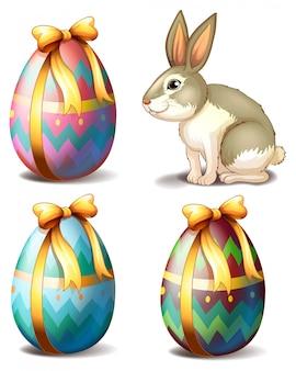 Drie kleurrijke eieren en een schattig konijntje