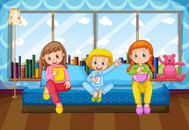 Drie meisjes die in slaapkamer eten en drinken