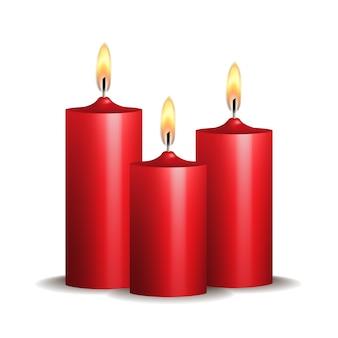 Drie rode brandende kaarsen op witte achtergrond.