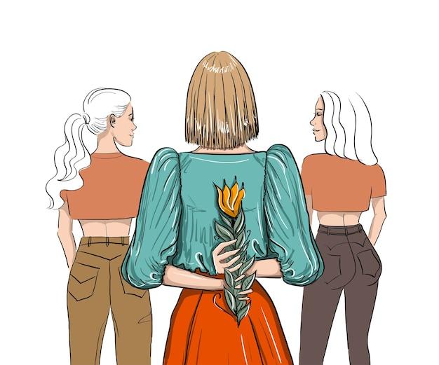 Drie vrouwen van achter met één bloem