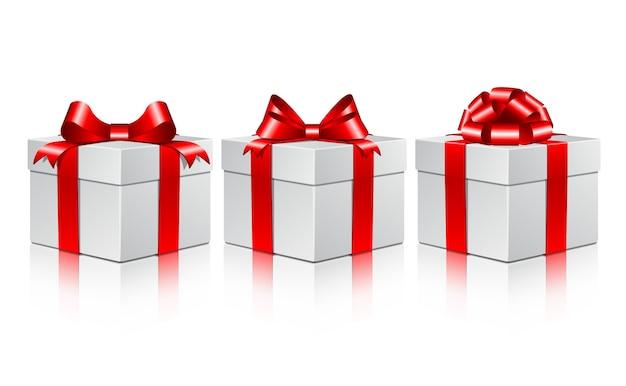 Drie witte geschenkdozen met een rode bogen.