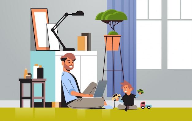 Drukke vader freelancer thuis werken met laptop zoontje spelen met speelgoed freelance quarantaine